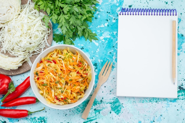 Vista dall'alto di verdure fresche a fette insalata di pezzi lunghi e sottili all'interno della piastra con peperoni verdi su sfondo blu brillante cibo pasto insalata di verdure