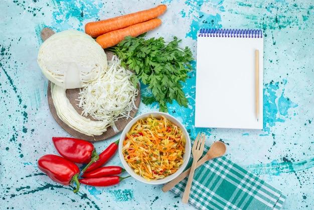 Vista dall'alto di verdure fresche a fette insalata lunga e sottile a pezzi all'interno del piatto con peperoni verdi sulla scrivania blu brillante cibo pasto insalata di verdure