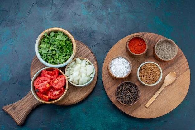 上面図スライスした新鮮な野菜のトマトと玉ねぎ、紺色のデスクフードディナー野菜料理に緑の調味料