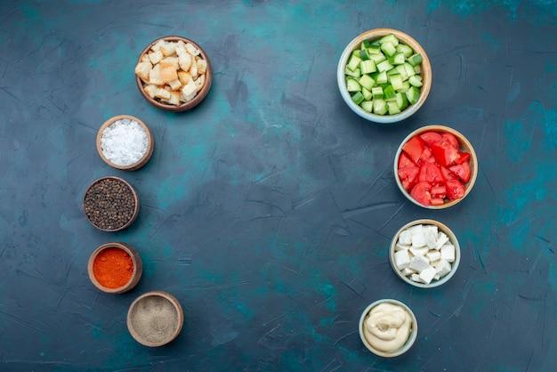 Vista dall'alto di verdure fresche a fette con salse condimenti salse sulla cucina di condimento pasto cibo scuro scrivania