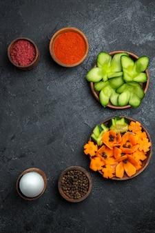 上面図暗い背景の調味料とスライスした新鮮な野菜サラダ健康野菜ミール食品