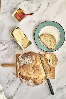 Vista dall'alto di un pane appena sfornato a fette su una tavola di legno con burro e marmellata