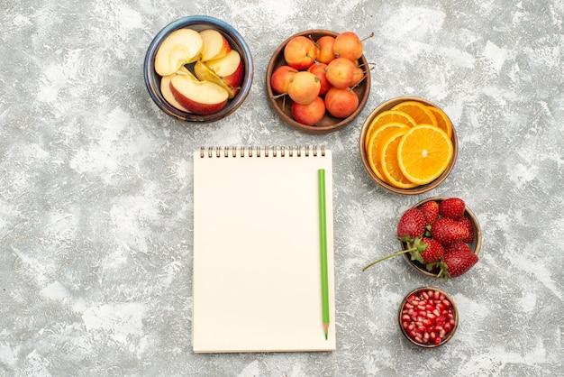 上面図スライスしたフルーツリンゴとオレンジとベリーの白い背景フルーツ新鮮なまろやかなビタミンの健康