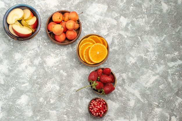 Top view sliced fruits apples and oranges with berries on light background fruit fresh mellow vitamine health