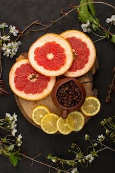 갈색 나무 책상과 어두운 바닥에 커피와 함께 자몽과 레몬과 같은 상위 뷰 슬라이스 과일 citruses