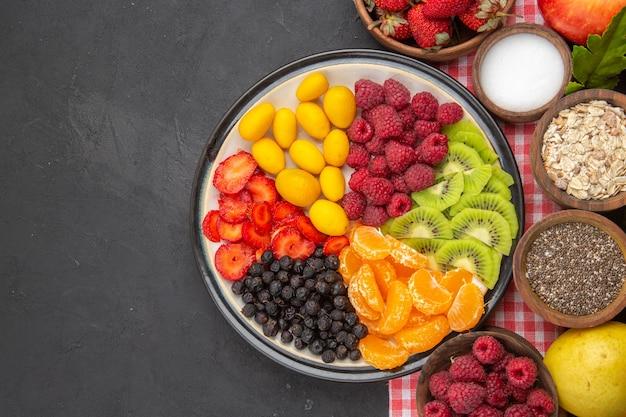 暗い背景に新鮮な果物とスライスした果物の上面図