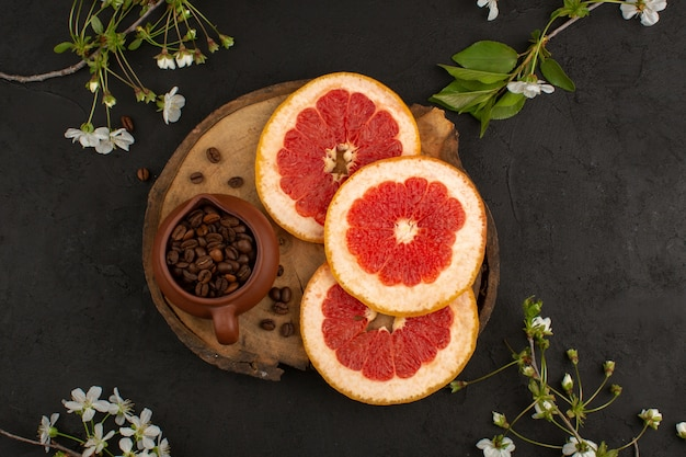 Top view sliced grapefruit fresh mellow juicy along with coffee seeds on the brown desk on the dark background