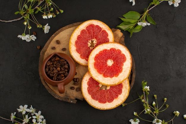 暗い背景に茶色の机の上のコーヒーの種子と共にグレープフルーツの新鮮でまろやかなジューシーなスライストップビュー