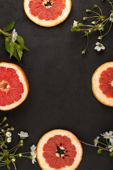 Top view sliced grapefruit juicy along with white flower on the dark background