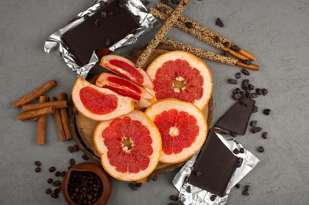 灰色の机の上のスライスグレープフルーツシナモンとチョコバーのトップビュー
