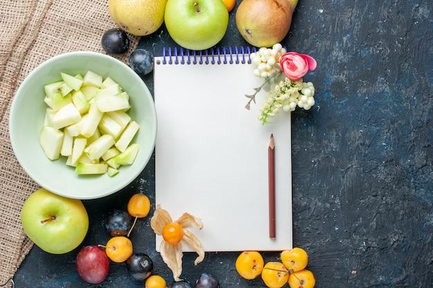 Vista superiore affettata mela verde insieme a diversi tipi di frutta fresca e blocco note sullo sfondo blu scuro biscotto di frutta dolce fresco
