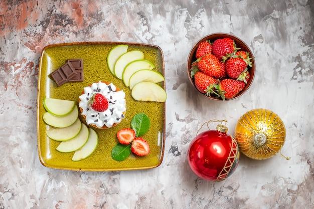 상위 뷰는 밝은 배경에 딸기와 케이크와 함께 녹색 사과 슬라이스