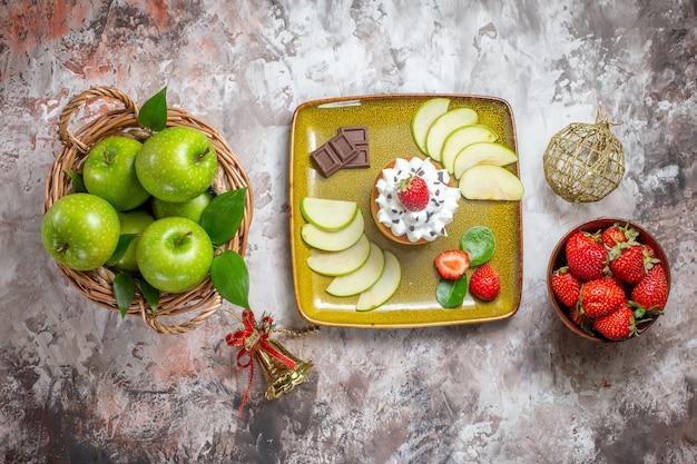 Vista dall'alto di mele verdi a fette con fragole e torta su sfondo chiaro
