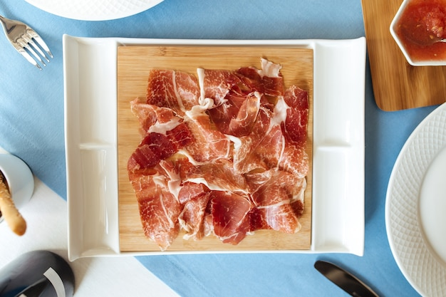 Top view on sliced jamon meat on the restaurant table