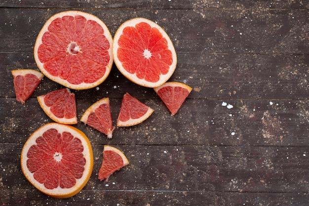 Вид сверху нарезанных сочных грейпфрутовых колец, образованных свежими на коричневом
