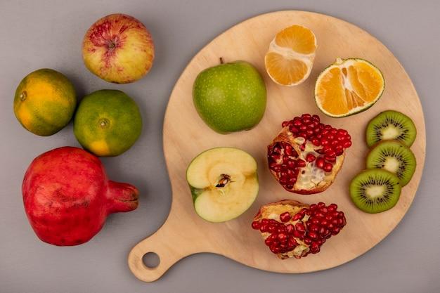 Vista dall'alto di kiwi a fette con mandarino e melograno tagliati a metà su una tavola di cucina in legno
