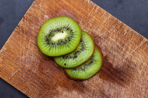 Top view of sliced kiwis on a wooden board on the table