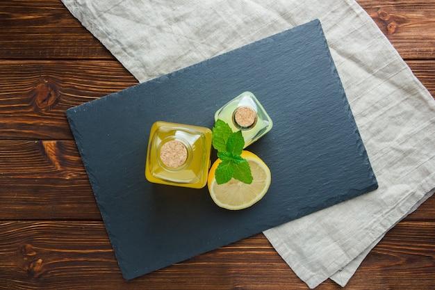 Top view sliced lemon in bowl with black cardboard, juice bottles on wooden surface.