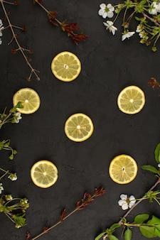 Vista dall'alto fette di limoni aspro morbido succoso intorno fiori bianchi sulla scrivania scura