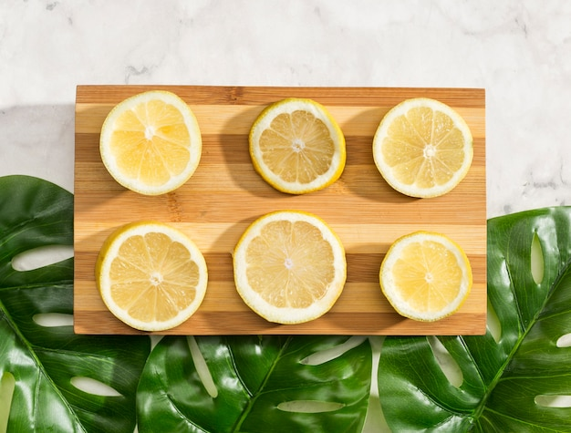 Top view sliced lemons on wooden board