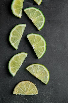 Top view of sliced limes on black surface