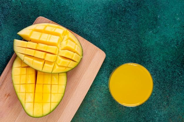 Vista dall'alto affettato mango su una lavagna con un bicchiere di succo d'arancia su un tavolo verde