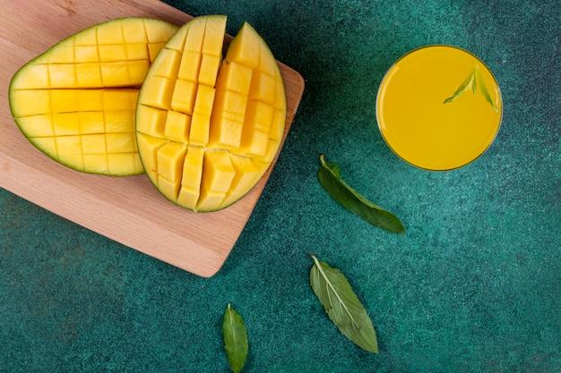 Vista dall'alto mango a fette su una lavagna con un bicchiere di succo d'arancia