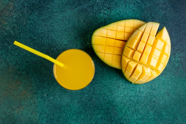 Вид сверху нарезанный манго со стаканом апельсинового сока на зеленый