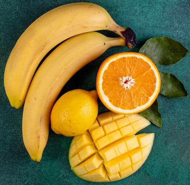 Вид сверху нарезанный манго с бананами половиной апельсина и лимоном на зеленом