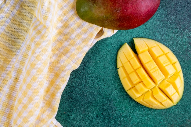 Top view sliced mango with a yellow kitchen towel on a green table