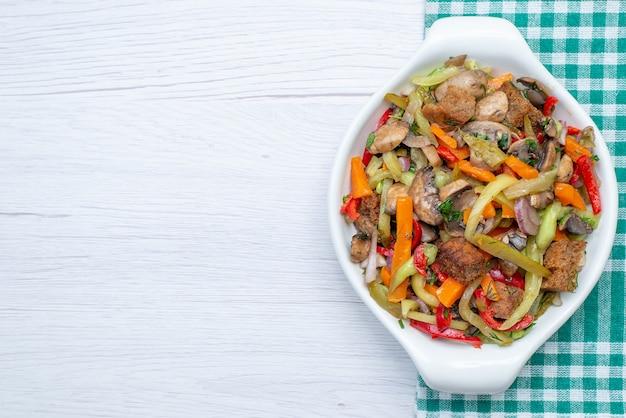 Vista dall'alto piatto di carne a fette con verdure cotte all'interno della piastra sulla carne vegetale di sfondo chiaro cibo pasto