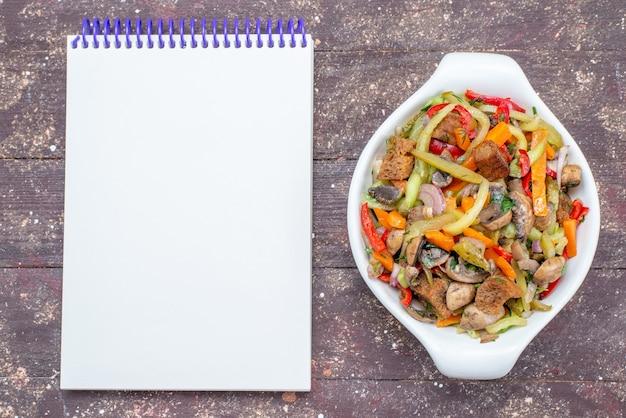 Vista dall'alto piatto di carne a fette con verdure cotte all'interno della piastra con blocco note sul piatto di carne vegetale di sfondo di legno marrone cibo pasto