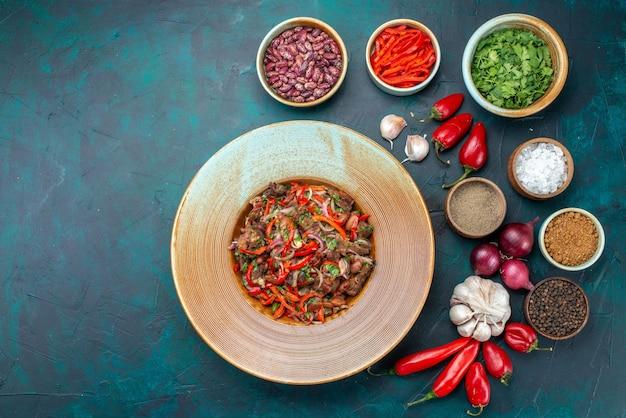 上面図スライスした肉と野菜、玉ねぎ、にんにく、紺色の机の上の野菜料理の食事の材料