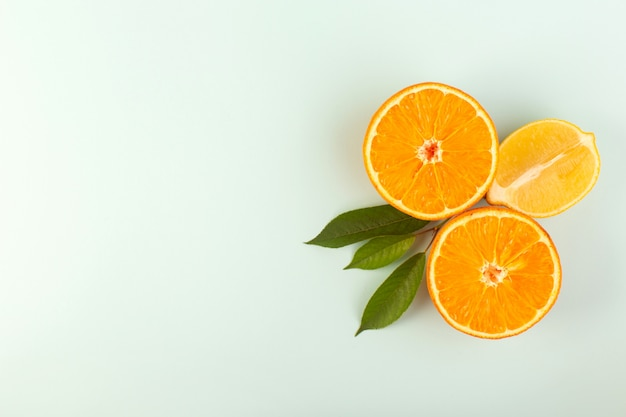A top view sliced orange fresh ripe juicy mellow isolated half cut pieces with green leaves on the white background fruit color citrus