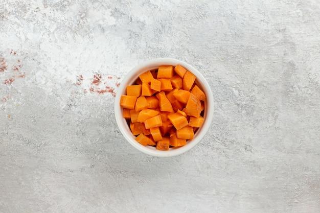 白い背景の上の小さな鍋の中のオレンジ色の野菜をスライスした上面図