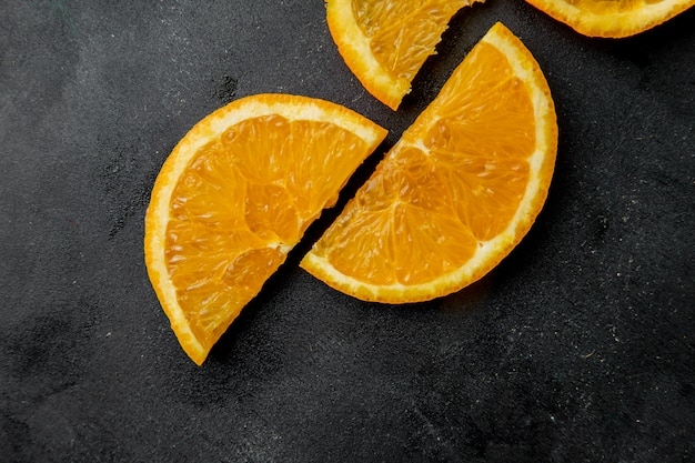 Top view of sliced oranges on black surface