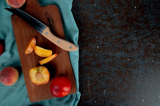 Top view of sliced peach with knife on cutting board with whole peaches on cloth on brown and black surface with copy space
