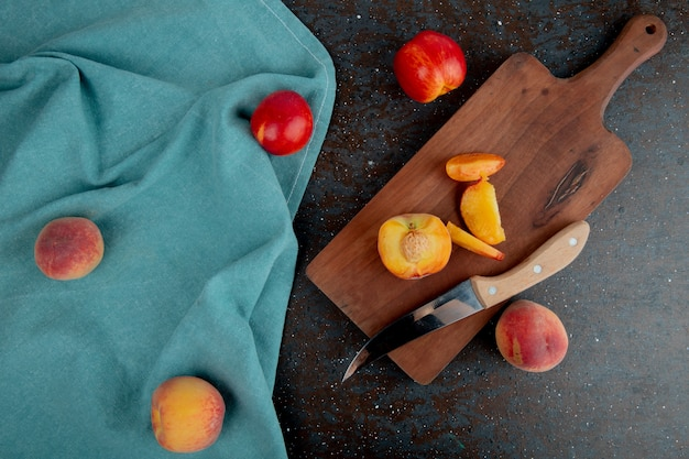 Top view of sliced peach with knife on cutting board with whole peaches on cloth on brown and black surface