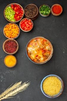 Vista dall'alto di pepe a fette con diversi condimenti e zuppa su uno sfondo grigio insalata di salute vegetale piccante pasto