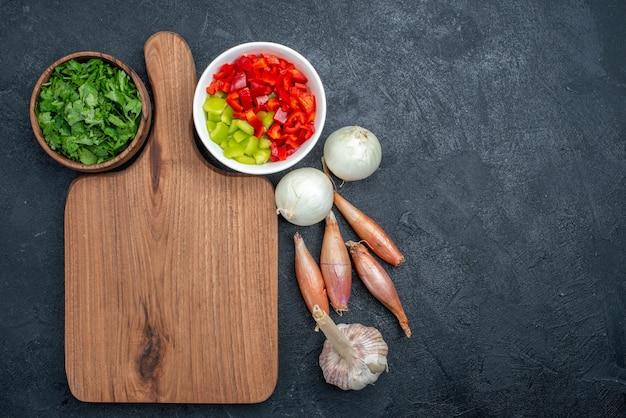 Pepe a fette vista dall'alto con aglio e verdure su spazio grigio