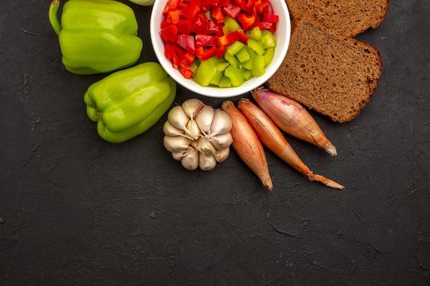 暗い机の上に野菜と暗いパンのパンとスライスしたコショウの上面図