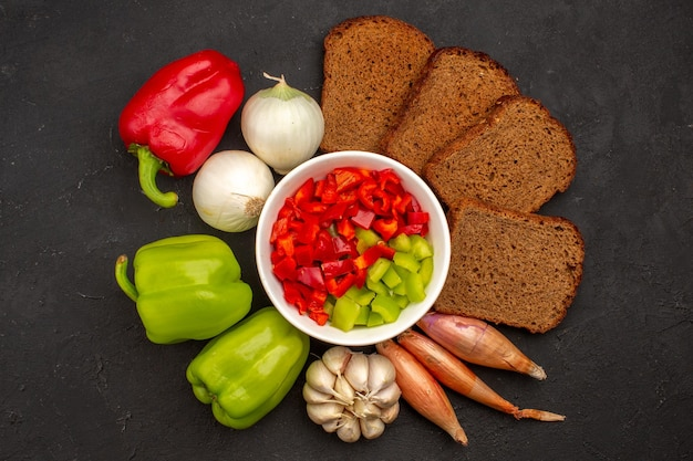 Top view sliced pepper with vegetables and dark bread loafs on dark space