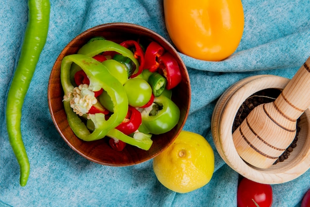 Top view of sliced peppers in bowl with whole ones and tomato lemon with black pepper in garlic crusher on blue cloth