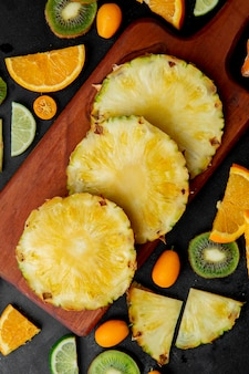 Top view of sliced pineapples on cutting board and other fruits around on black surface