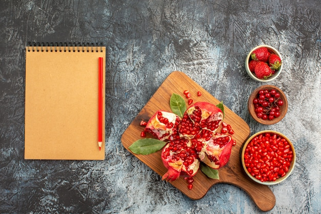 Top view of sliced pomegranates with red fruits on dark background