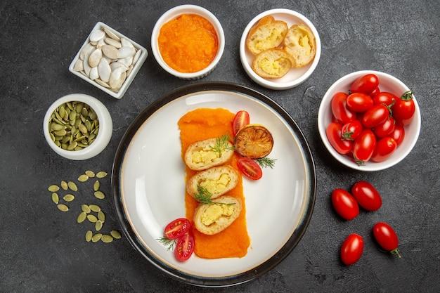 ダークグレーの背景に新鮮な小さなトマトとスライスしたポテトパイの上面図パイ焼きオーブンホットケーキケーキ