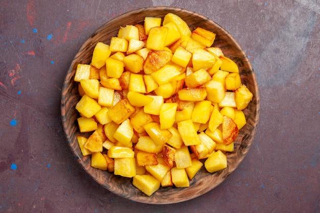 Vista dall'alto patate a fette all'interno del piatto marrone sul buio