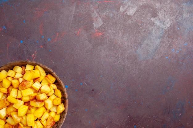 暗闇の中で茶色のプレート内のスライスされたジャガイモの上面図