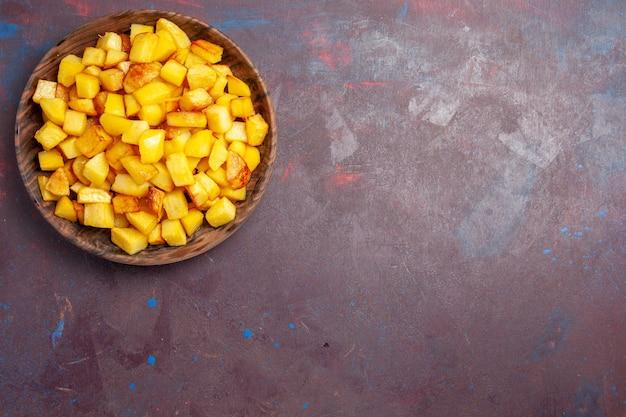 어둠에 갈색 접시 안에 감자 슬라이스 상위 뷰