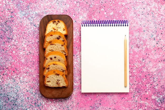Top view sliced raisins cake with notepad on pink surface